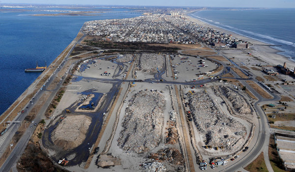 Huge piles of debris at Jacob Riis Park in the Rockaways await transfer to the Fresh Kills landfill and then upstate. Photo from the New York Times.