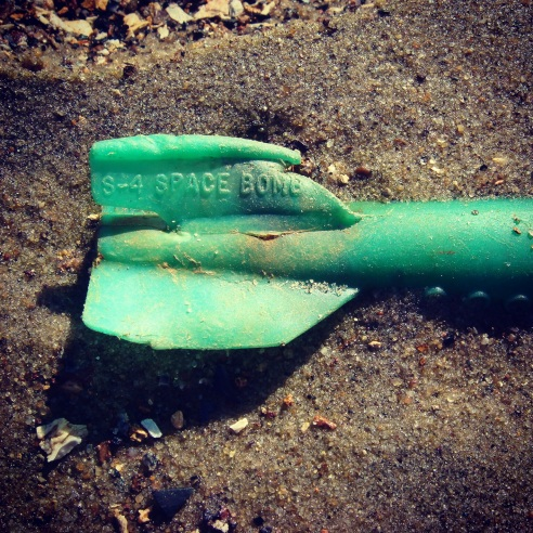 Howard Warren and his students research the waste at Deadhorse Bay, and have dated most of the waste escaping the landfill as circa 1930s. One of the dating methods is identifying objects like this. Plastics were introduced as consumer items on either side of World War II, and they can use the serial number on this plastic toy missile to identify when it was manufactured, and thus when it was probably disposed of. Photography by Max Liboiron.