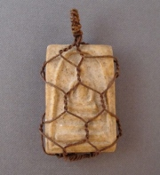 """Thai Buddha amulet, c.1920. """"This small pottery amulet has an image in relief of Somdej, a Buddhist monk and son to King Rama II, meditating on a coiled snake, and was found in a temple in Siam (Modern Thailand) in the first part of the 19th century. These are typically found snugly fitted into tiny metal frames, allowing the amulet to be worn by a worshiper. In this case, the metal frame broke off and the owner or a tinker came up with a fast and economical remedy by encasing the amulet in what looks like small scale chicken wire."""""""