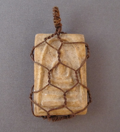 "Thai Buddha amulet, c.1920. ""This small pottery amulet has an image in relief of Somdej, a Buddhist monk and son to King Rama II, meditating on a coiled snake, and was found in a temple in Siam (Modern Thailand) in the first part of the 19th century. These are typically found snugly fitted into tiny metal frames, allowing the amulet to be worn by a worshiper. In this case, the metal frame broke off and the owner or a tinker came up with a fast and economical remedy by encasing the amulet in what looks like small scale chicken wire."""