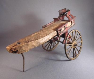 "Cast iron horse drawn ladder wagon, c.1900. ""A small cast iron fragment is all that remains of an elaborate miniature horse drawn ladder wagon. Someone loved their toy almost ""to death"" and I am grateful to whoever nailed the remains to a scrap of wood, breathing new life in to their cherished plaything."""