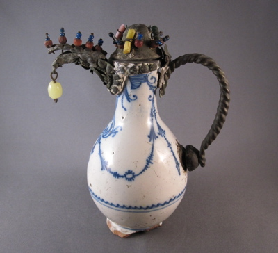 "French Delft ewer, c.1690 Elaborate metal mounts with dangling glass ""jewels"" replace the original ceramic spout, handle and cover."