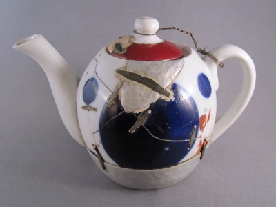 "Eastern European teapot, c.1925. ""No part of this poor teapot has escaped damage, making it by far the most altered piece in my collection. There are 18 metal support staples, a replaced hand-hammered tin base, a large tin patch on one side, a mended chip on the lid grafted from another lid entirely, and a wire tether holding the lid in place. The  numerous metal staples (aka rivets) appear to be machine made and are reinforced with cement."""