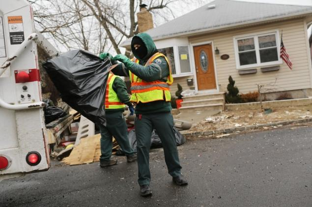Sanitation workers remove debris from a flood-damaged Staten Island home. Now, some Sanitmen are contesting their post-hurricane cleanup pay. Photo by Spencer Platt. February 26, 2013.