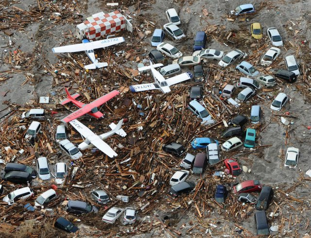 Light planes and vehicles sit among the debris after they were swept by a tsunami that struck Sendai airport in northern Japan on Friday March 11, 2011. Image by By Kansan Staff.