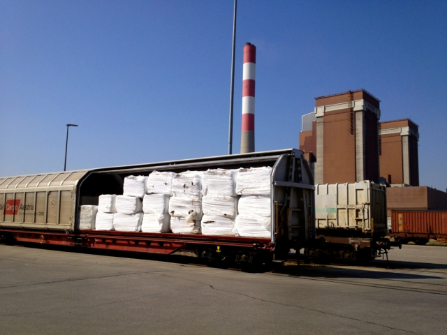 Rail cars with prepared waste bales, potentially from Italy or Slovenia. The two towers and chimney of the coal-fired power plant are visible behind the yard. Author's photo.