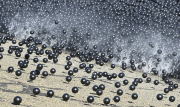 black balls hitting the water
