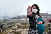 This image of a pregnant Inuk woman was taken during a four month long dump fire that occurred in the Arctic community of Iqaluit, Nunavut. During the fire, pregnant women and women of childbearing age were warned not to go outside due to risks of dioxin contamination. The Inuktitut syllabics written on her hand read 'Taima' or 'enough', referring to decades of government underfunding that contributed to this and many other dump fires. The image is an example of refusal, as the image refuses to depict Inuit as passive victims of slow violence, instead redirecting attention towards government institutions. The image was distributed to media outlets and became the Facebook profile photo of a local 'Stop the Dump Fires' protest group. Photo by Shawn Inuksuk, 2014.