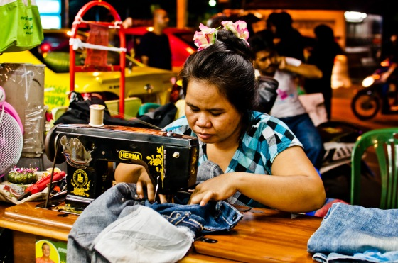 A seamstress repairs a pair of jeans at her streetside sewing stand on Sukhumvit Soi 3 in Bangkok, Thailand.  These foot-powered sewing machines are a common sight along many streets in Bangkok.